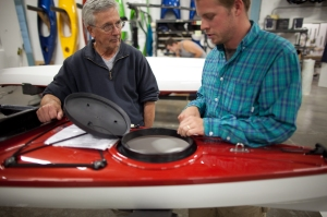 Owner and Thermoform Expert Tom Derrer (left) showing Sanergy's Mike Hahn some design details on the latest Fathom sea kayak