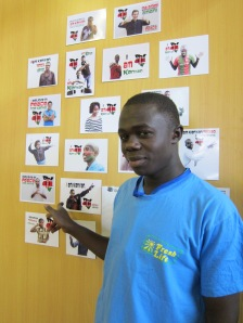 Sanergy team member Oliver in Sanergy's office, gesturing towards his I Am Kenyan portrait