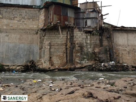 A toilet emptying untreated waste into a river in Nairobi, Kenya with evidence of open defecation in the foreground