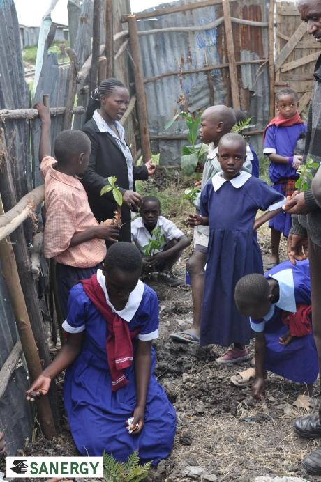 Jaombi Foundation Primary School Principal Jackline Mogoi instructing her students in tree planting.