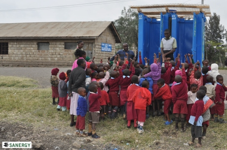 Sanergy team members  James Mbugua and Peter Macharia instructing Baptist Primary School students in proper Fresh Life Toilet use.